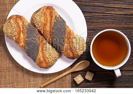 Cup of tea and buns with sesame and poppy seeds in plate on wooden table top view
