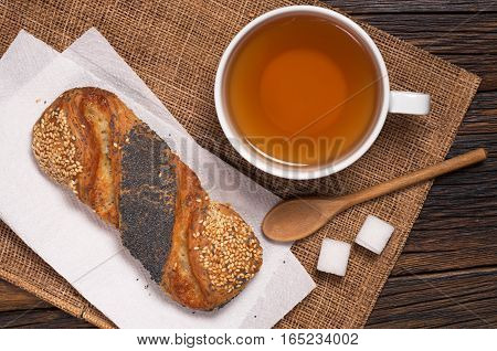 Cup of tea and buns with poppy seeds and sesame on wooden table top view