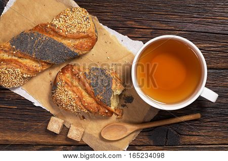 Cup of tea and buns with poppy seeds and sesame on dark wooden table top view