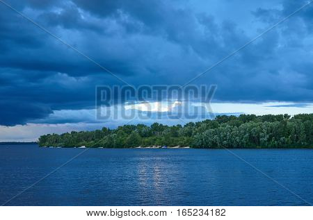 Landscape. The wide river the sandy coast of the river overgrown with deciduous forest. In the sky cumulonimbus