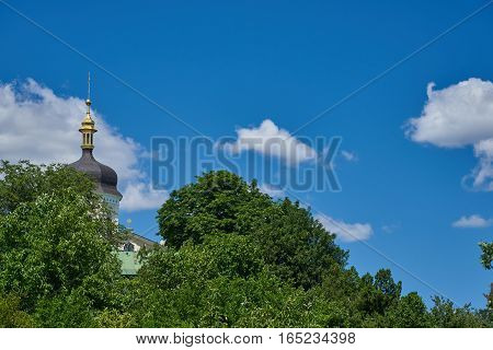 Landscape with tree and the dome of the Orthodox church against the blue sky with cumulus clouds