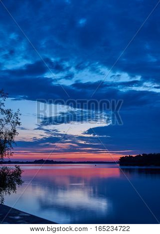 Landscape. Dawn over the broad river. River forest thickets beach. The sky is clouded over