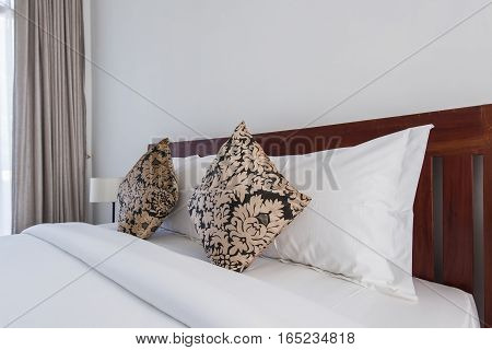square brown pillows on a double bed in bedroom.