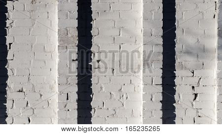 White brick wall with two columns in the middle with a long shadow clean white architectural background white horizontal brick texture