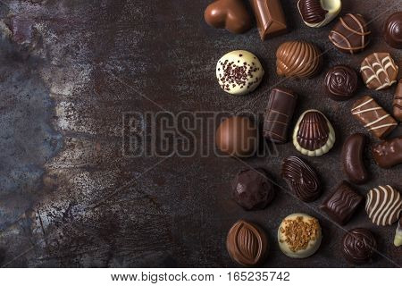Assortment of fine chocolate candies white dark and milk chocolate. Sweets background with copy space. Top view