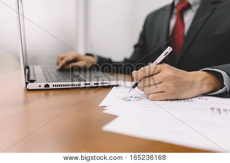 Businessman working with business document and laptop on the table