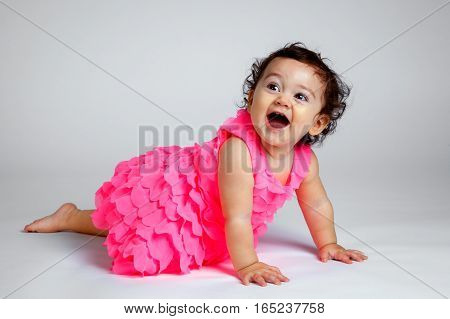 An adorable and very happy baby on a white background looks up and smiles as she is crawling. Her eyes are big and bright and her mouth is wide open. She looks excited.
