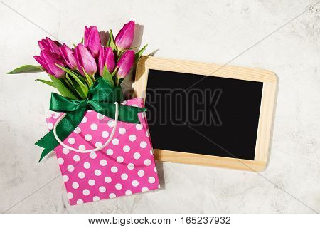 Fresh beautiful lila tulips in gift package on marble background with chalkboard. Spring concept. Horizontal top view with copy space.