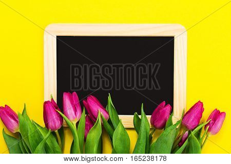 Fresh beautiful lila tulips on yellow colorful background with chalkboard. Spring concept. Horizontal top view with copy space.