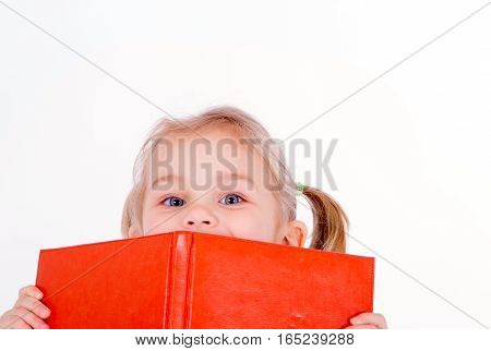 little adorable girl peeking from behind the orange note book
