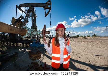 Beautiful woman engineer in the oilfield wearing red helmet and work clothes. Pump jack and wellhead valve background. Oil and gas concept.