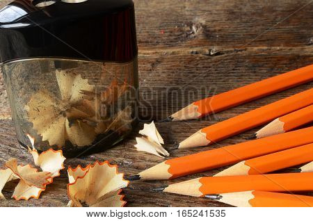 A close up image of several sharpened pencils and one black pencil sharpener.