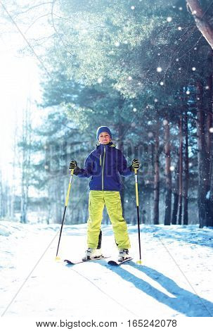 Skier child boy in winter sportswear with ski over sunny forest