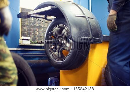 The process tire service tyre wheel of car in motion with workers