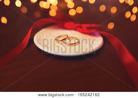 Wedding two gold rings on the table with red ribbon over celebration light bokeh background