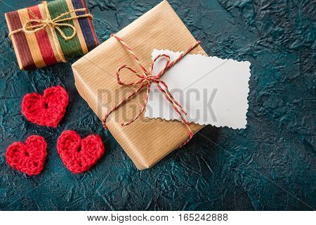 Crochet valentine hearts, gift box and a greeting card on a dark background