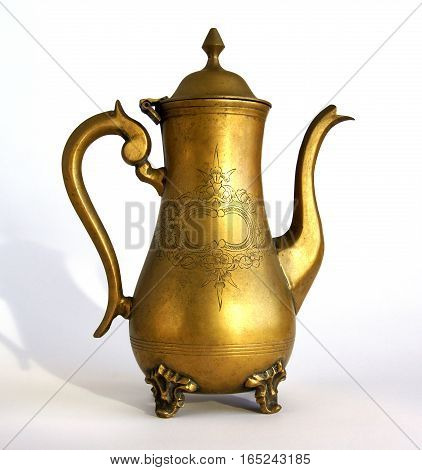 Antique brass coffeepot with a pattern on white background with shadows