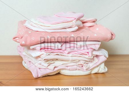 Pile of clothes for newborn girl on wooden background with toy.