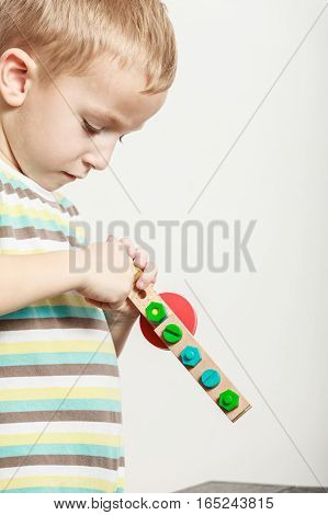 Spending free time play and education for children. Little boy in striped shirt play with colorful toy.