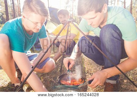 Guys making meal near the tent in the woods