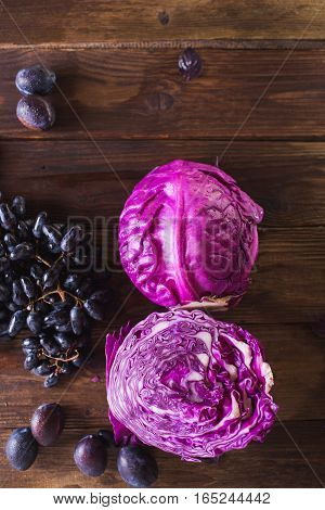 Blue cabbage and grapes on a wooden background. Copyspace