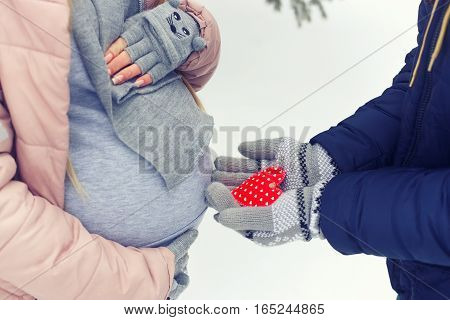 Couple waiting for baby in winter. Love, family, pregnancy concept. Close up pregnant belly and a man's hands with red heart. Young couple. A pregnant woman. Tummy.