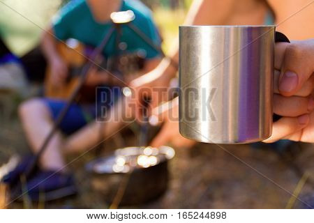 Close-up shooting of metal cup being hold by the guy. In the background one of tourists playing guitar