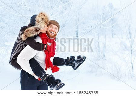 Happy winter couple. Man giving woman piggyback ride on winter vacation in snowy forest. Winter fun couple playful together outdoor. Valentine's Day and love concept. Girl kisses man in winter forest