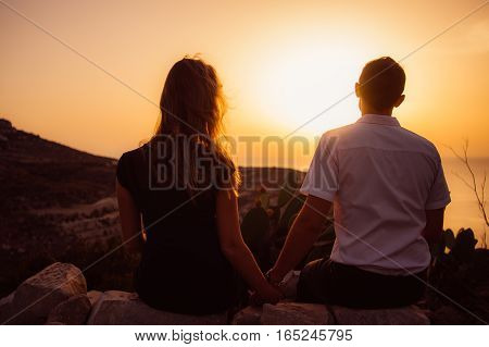 Couple Sitting On Rock In The Evening On The Seaside