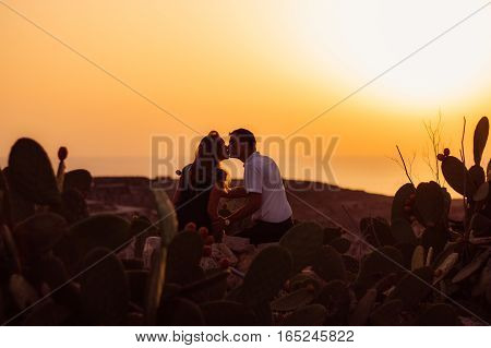 Couple Sitting On Rock In The Evening