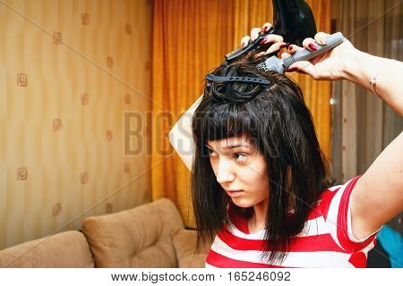 Girl dries hair and makes the hairstyle in her room. She uses the Hairdryer and comb. The home interior 7
