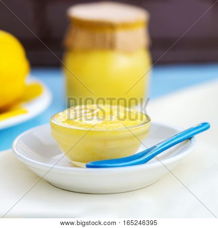 square image of fresh organic homemade lemon curd showing lemons and lemon curd in a jar and glass dish pretty with light blue and yellow colors room for copy space