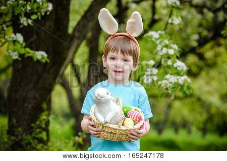Little Boy Hunting For Easter Egg In Spring Garden On Day. Cute Child With Traditional Bunny Celebra