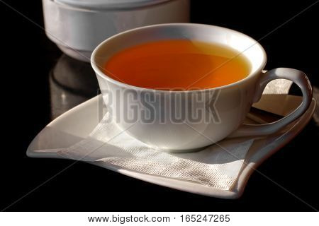 Cup of black tea on a saucer with a napkin and sugar bowl on a dark background