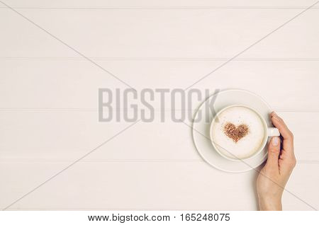 Female hand holding cup of coffee on white wooden table. Photograph taken from above, top view with copy space