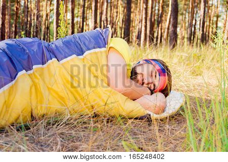 Guy sleeping in the sleeping-bag on the ground in the woods