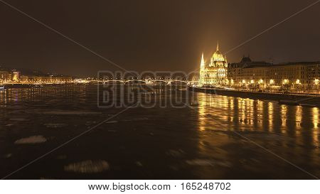 Parliament at nighttime with icy Danube river
