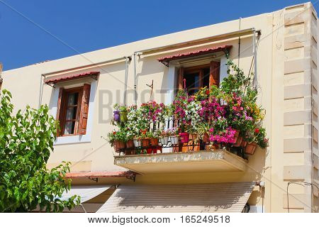Rethymnon Island Crete Greece - June 23 2016: A balcony with lot of pots with flowers in the second part of old house located in Old Town of Rethymnon
