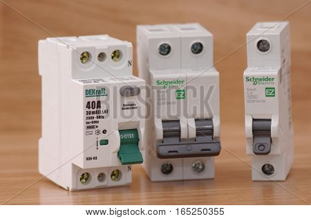 SARANSK, RUSSIA - JANUARY 13, 2017: DEKraft residual-current device and Schneider Electric circuit breakers on wooden background.