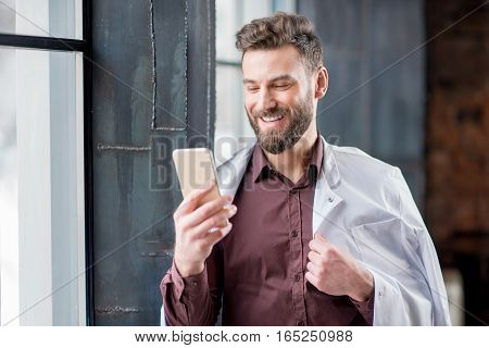 Portrait of handsome confident doctor with medical gown with smart phone standing near the window in the modern dark interior clinic or office