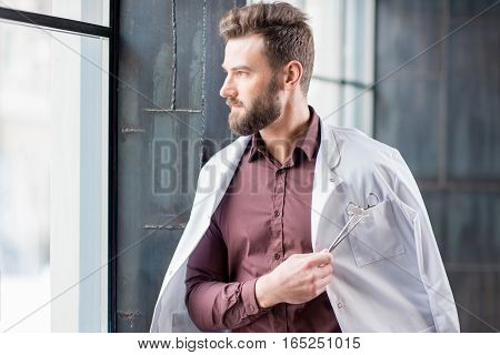 Portrait of handsome confident doctor with medical gown standing near the window in the modern dark interior clinic or office