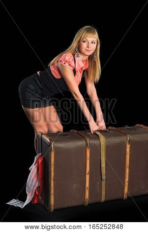 Beautiful girl with smile holds vintage suitcase, isolated on black background