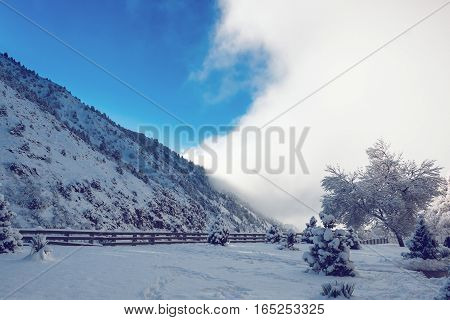 Pictersque landscape of snowy mountains partially covered by clouds