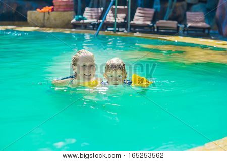 Young Cheerful Mother And Son In A Swimming Pool