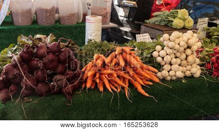 Red beets, orange carrots, and white and red radishes at an organic farmer's market