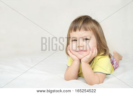 Smiling Happy Little Girl Lying On Bed