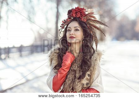 The girl in a fur vest, red gloves and a wreath on a background of a winter landscape