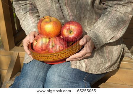 Woman in blue jeans and gray stripe shirt sits on porch of wooden  house and holds wooden bowl with ripe appetizing apples on sunny day. Close up photo