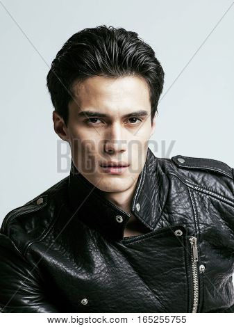 young handsome man, leather jacked on naked torso, emotional posing, white background, modern guy, lifestyle people concept close up