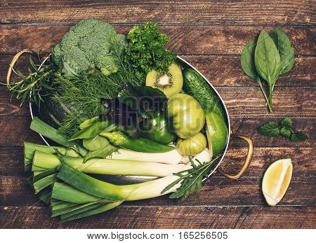 Retro styled food background. Raw detox green vegetable and herbs in old copper stew pot ready for cooking on rustic wooden background